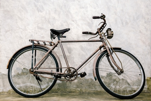 Antiga bicicleta vintage enferrujada perto do muro de concreto