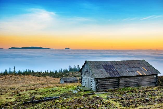 Antiga cabana rural em frente a uma bela natureza com nuvens oceano, montanhas e campos de grama