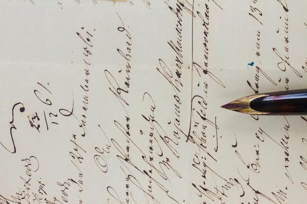 Antiga caneta de pena dourada no fundo de uma carta manuscrita, close-up