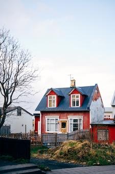 Antiga casa clássica vermelha com telhado azul e janelas no telhado em reykjavik, a capital da islândia