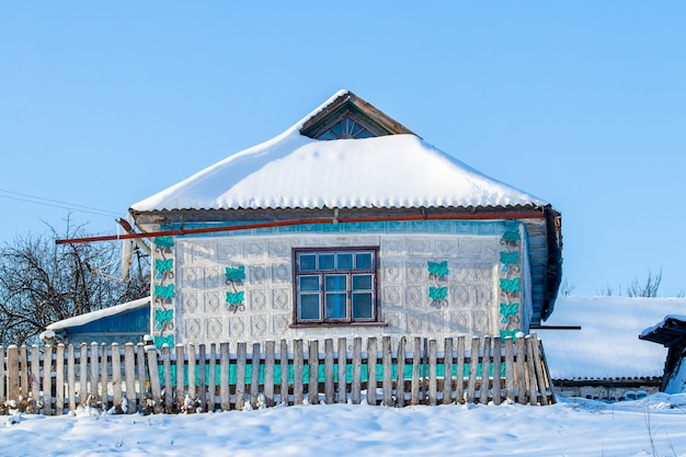Antiga casa de aldeia no inverno em tempo ensolarado. a aldeia no inverno