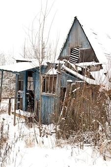 Antiga casa de campo abandonada e destruída no inverno