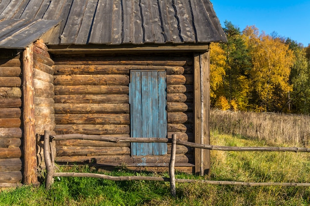 Antiga casa de campo feita de troncos. porta de madeira para o quintal. uma cerca feita de vigas de madeira.