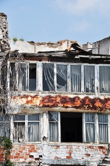 Antiga casa de tijolos. caixilharia sem vidro. telhado de metal desmontado.