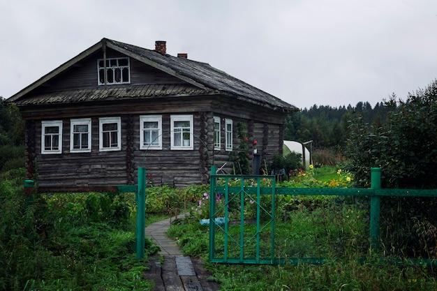 Antiga casa de toras de madeira com uma horta na aldeia.