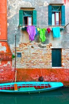 Antiga casa no canal de veneza com barco de madeira atracado, itália