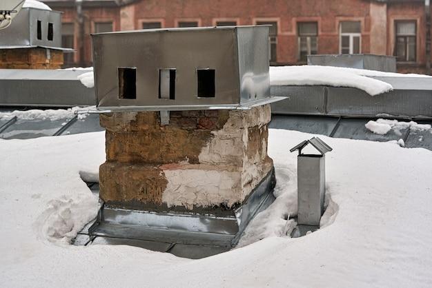 Antiga chaminé de tijolos em um telhado de neve