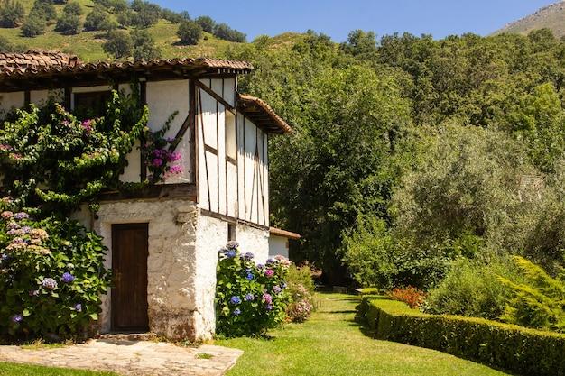 Antiga e tradicional casa espanhola entre vegetação verde.