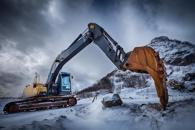 Antiga escavadeira em paisagem de inverno