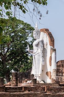 Antiga estátua branca de buda está de pé na igreja antiga.