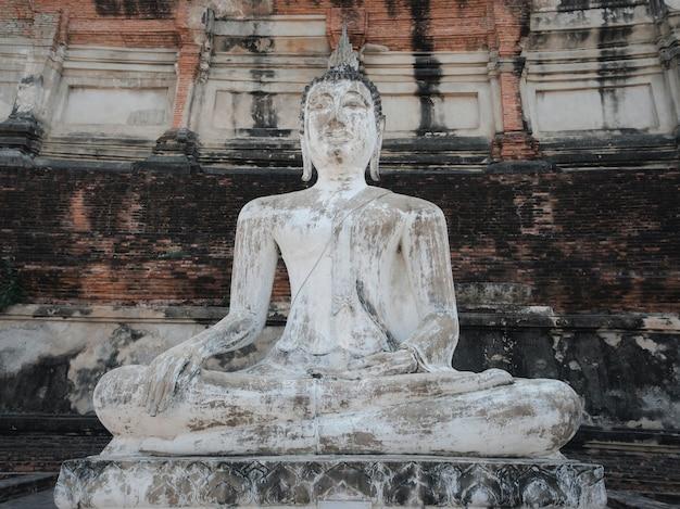 Antiga estátua de buda branca com fundo de parede de pagode no templo budista wat yai chai mongkhon na província de phra nakhon si ayutthaya, tailândia
