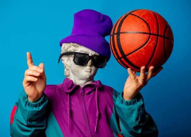 Antiga estátua vestida com roupas da moda dos anos 90 segura bola de basquete