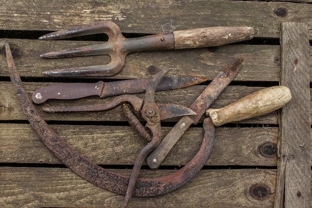 Antiga ferramenta de jardinagem em uma mesa rústica