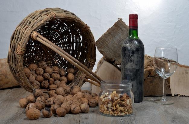 Antiga garrafa de vinho com uma cesta de nozes