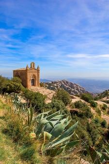 Antiga igreja de pedra no topo da colina em um dia ensolarado de verão. montanhas de montserrat na espanha. foto vertical.
