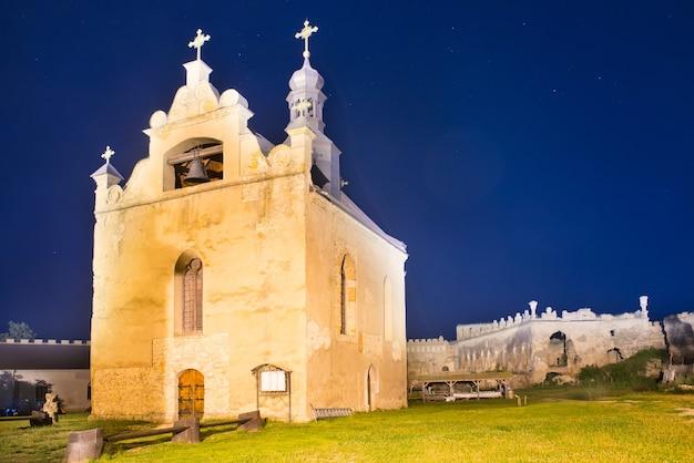 Antiga igreja em um castelo medieval à noite sob um céu azul escuro com muitas estrelas