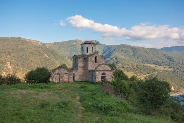 Antiga igreja nas montanhas, no parque nacional dombai, cáucaso, rússia. paisagem de verão, clima ensolarado, céu azul dramático e dia ensolarado