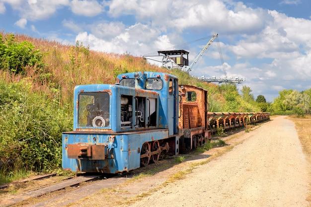 Antiga locomotiva rusty com uma linha de vagões de carvão e escavadeira de corrente de balde
