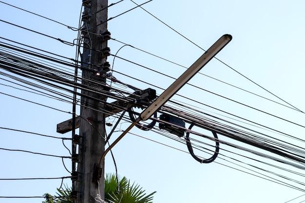 Antiga luz de rua no poste de concreto com emaranhado de cabos elétricos.