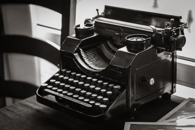 Antiga máquina de escrever manual na mesa do escritor, em frente à janela