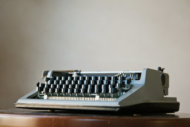 Antiga máquina de escrever retro clássica em uma mesa empoeirada contra um fundo bege de parede