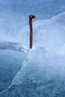 Antiga muleta ferroviária cravada no gelo de um lago. pino enferrujado e gelo derretendo azul com rachaduras e bolhas de ar. resistência e firmeza de símbolo. vertical.