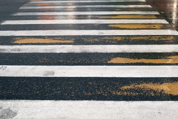 Antiga passagem de pedestres, marcações de estradas amarelas e brancas depois da chuva. perspectiva de cima.