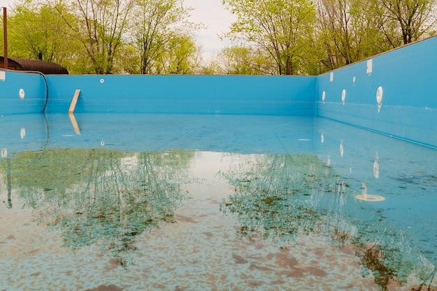 Antiga piscina azul suja cuidando de piscinas externas