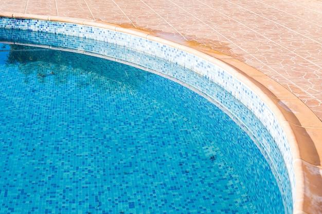 Antiga piscina no hotel com água azul.