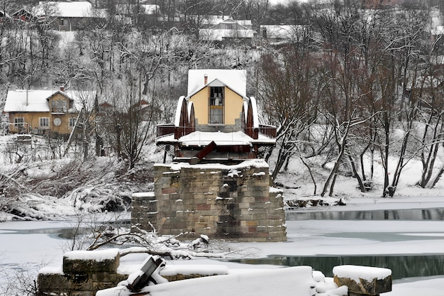 Antiga ponte de estrada de aço em ruínas sobre o rio após queda de neve