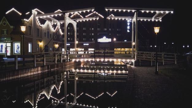 Antiga ponte de madeira iluminada refletindo no canal