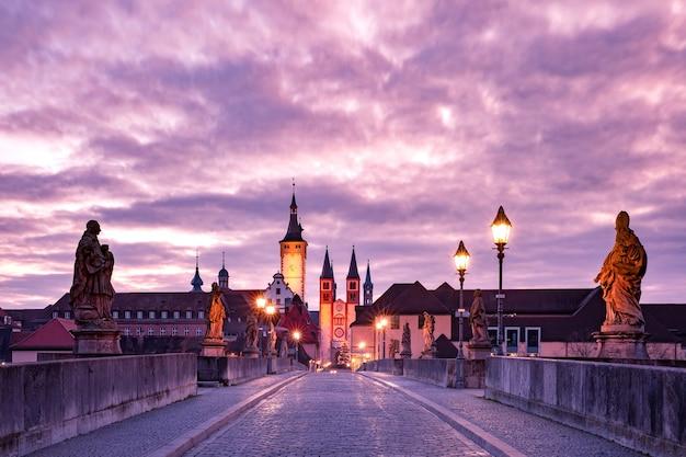 Antiga ponte principal, alte mainbrucke com estátuas de santos, catedral e prefeitura na cidade velha ao pôr do sol rosa, wurzburg, baviera, alemanha