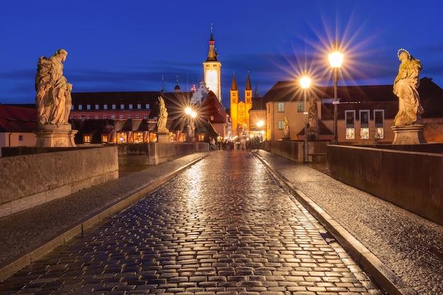 Antiga ponte principal, alte mainbrucke com estátuas de santos, catedral e prefeitura na cidade velha de wurzburg à noite, franconia, baviera, alemanha