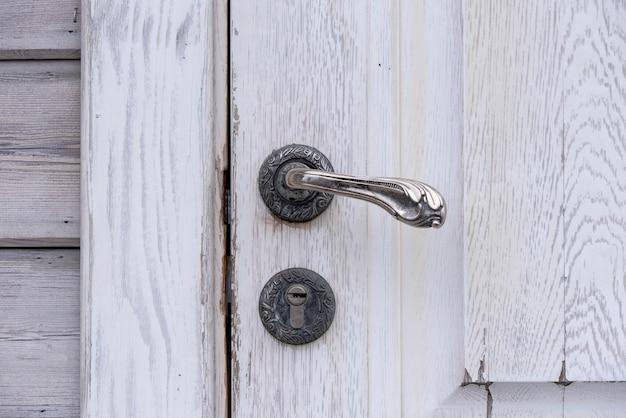 Antiga porta de madeira cinza vintage velha com alça de ferro e fechadura