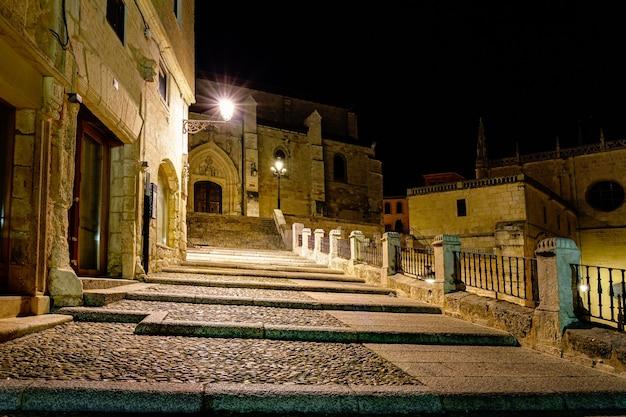Antiga rua da cidade medieval de burgos, iluminada à noite e ao lado da catedral. espanha.