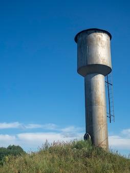 Antiga torre de água de metal em dia ensolarado no campo na rússia no verão.