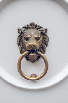 Antiga trava de metal em forma de cabeça de leão segurando o anel