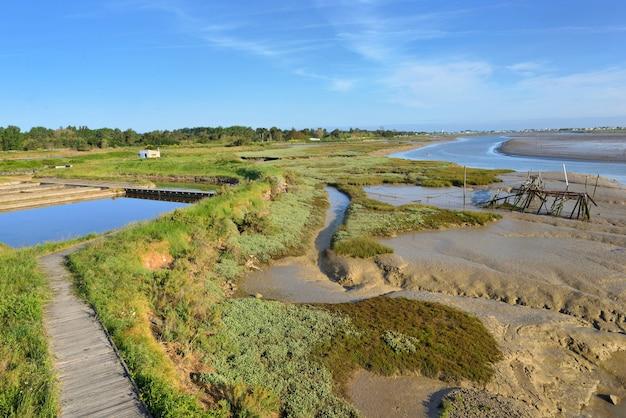 Antigas lagoas de água do mar para cultivo de ostras e trilha em um prado de madeira