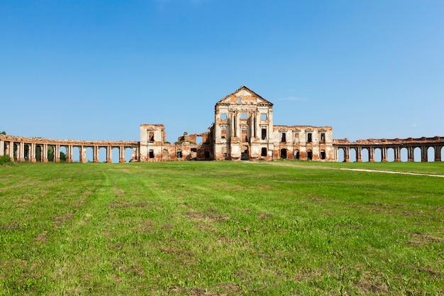 Antigas ruínas do castelo, temporada de verão. no fundo, céu azul, na terra cresce grama verde