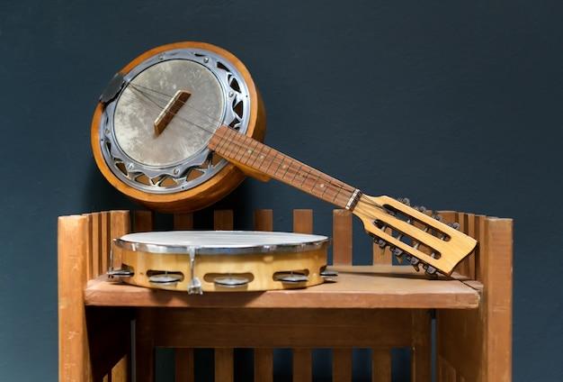 Antigo banjo de madeira e pandeiro em uma pequena prateleira