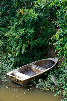 Antigo barco de fibra de vidro ancorado nas margens do rio