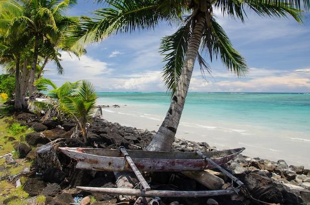 Antigo barco de madeira na costa cercado pelo mar e palmeiras na ilha savai'i, samoa