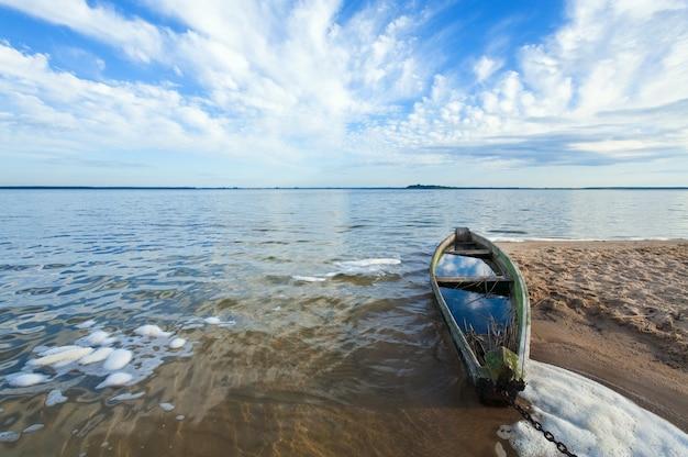 Antigo barco de pesca de madeira inundando perto da margem do lago e o céu de verão atrás (svityaz, ucrânia)
