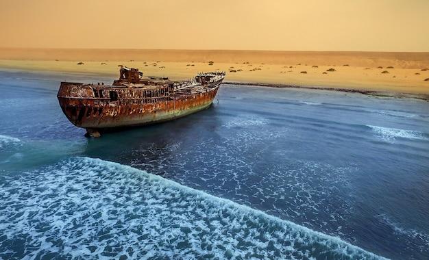 Antigo barco naufragado abandonado estande na praia