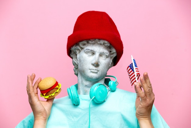 Antigo busto de macho no chapéu com a bandeira do eua e hambúrguer