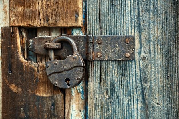 Antigo cadeado enferrujado no portão de madeira