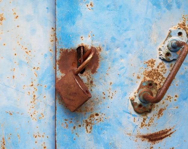 Antigo cadeado enferrujado pendurado em uma porta de metal azul