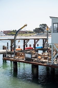 Antigo cais cheio de utensílios de pesca próximo a um porto
