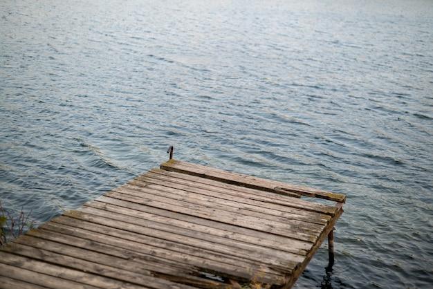 Antigo cais de madeira com tábuas danificadas na superfície ondulada do lago