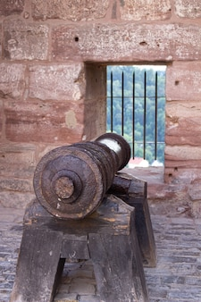 Antigo canhão preto apontando para uma abertura na muralha de um castelo com o mar ao fundo